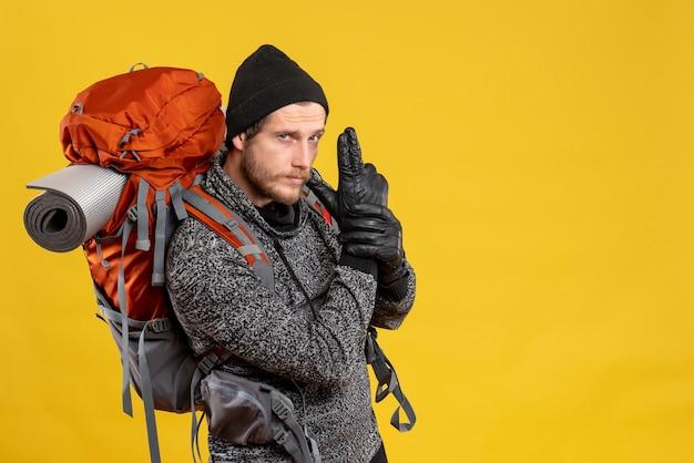 Auto-stoppeur masculin avec des gants en cuir et un sac à dos faisant un pistolet à doigt