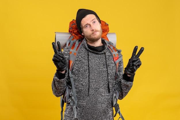 Auto-stoppeur masculin avec des gants en cuir et un sac à dos faisant le signe de la victoire