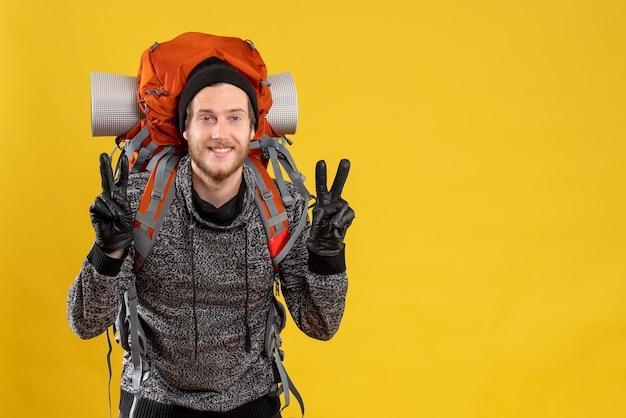 Auto-stoppeur masculin avec des gants en cuir et un sac à dos gesticulant signe v