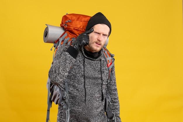 Auto-stoppeur masculin avec des gants en cuir et un sac à dos mettant le doigt pointé sur le temple
