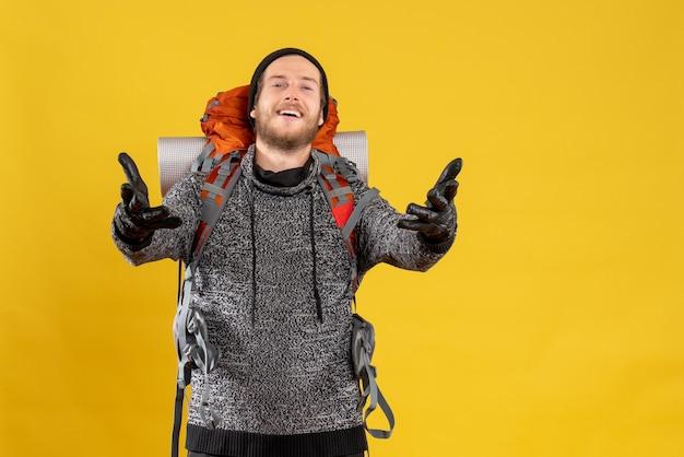 Auto-stoppeur masculin avec des gants en cuir et un sac à dos ouvrant les mains pour embrasser