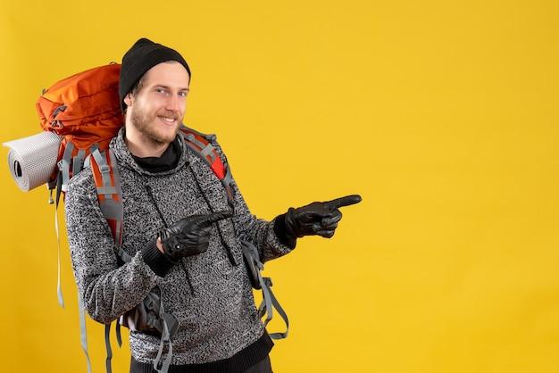 Auto-stoppeur masculin avec des gants en cuir et un sac à dos pointant les doigts dans la bonne direction