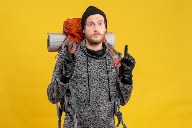 Auto-stoppeur masculin avec des gants en cuir et un sac à dos pointant les doigts vers le haut