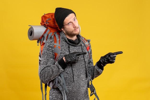Auto-stoppeur masculin avec des gants en cuir et un sac à dos pointant vers la droite