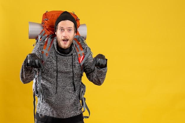 Auto-stoppeur masculin avec des gants en cuir et un sac à dos pointant vers le sol