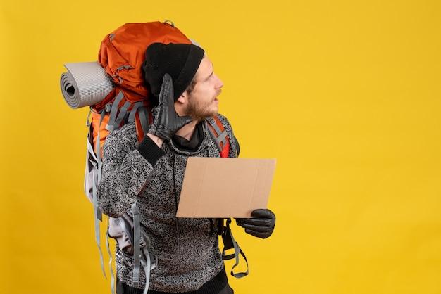 Auto-stoppeur masculin avec des gants en cuir et un sac à dos tenant un carton vierge écoutant quelque chose