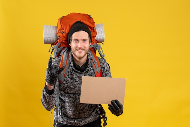 Auto-stoppeur masculin avec des gants en cuir et un sac à dos tenant un carton vierge faisant un signe de rock
