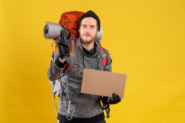 Auto-stoppeur masculin avec des gants en cuir et un sac à dos tenant un carton vierge montrant trois doigts