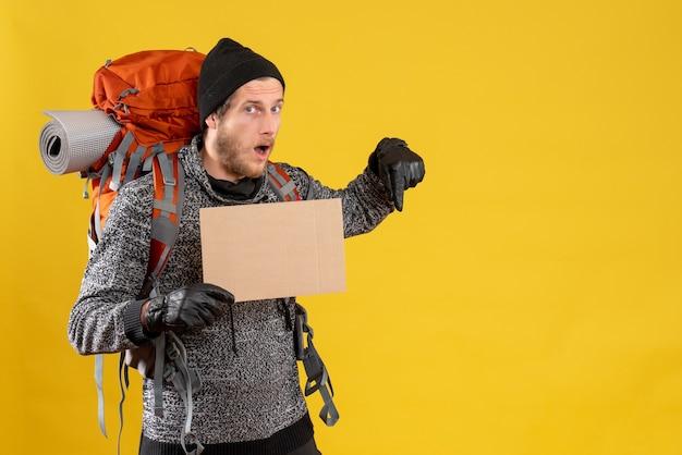 Auto-stoppeur masculin avec des gants en cuir et un sac à dos tenant un carton vierge pointant le doigt vers le bas