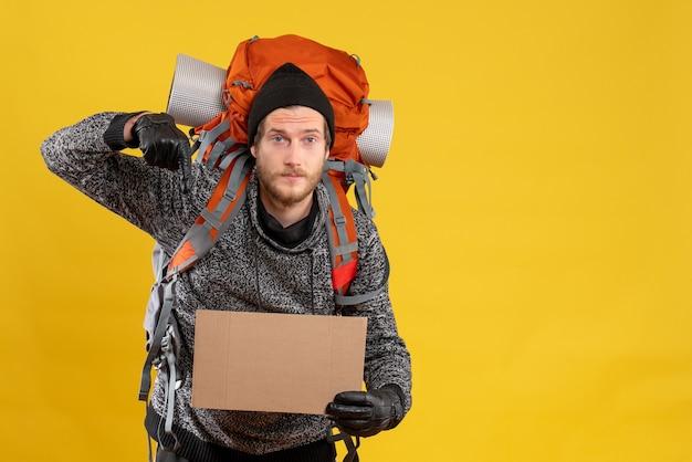 Auto-stoppeur masculin avec des gants en cuir et un sac à dos tenant un carton vierge pointant vers le sol