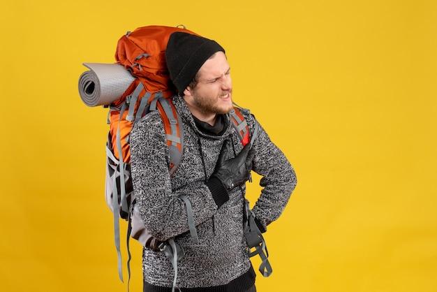 Auto-stoppeur masculin avec des gants en cuir et un sac à dos tenant le coeur avec la douleur