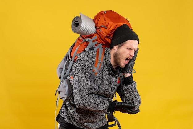 Auto-stoppeur masculin avec des gants en cuir et un sac à dos tenant les dents avec douleur