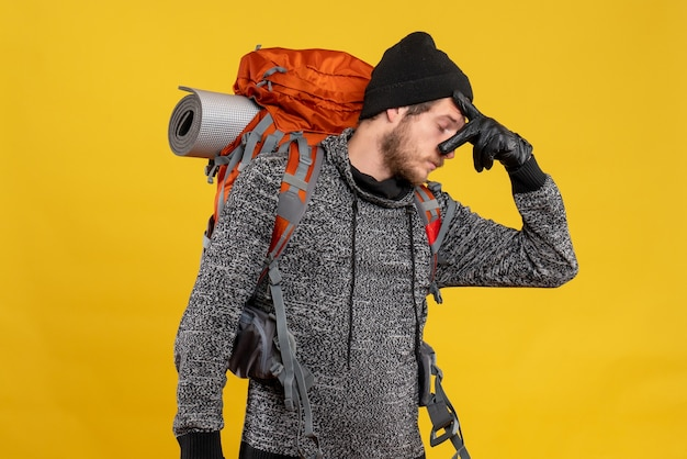 Auto-stoppeur masculin avec des gants en cuir et un sac à dos tenant son nez