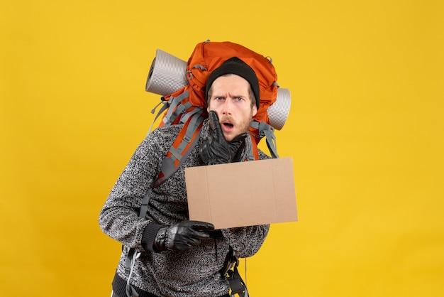 Auto-stoppeur masculin sceptique avec des gants en cuir et un sac à dos tenant un carton vierge