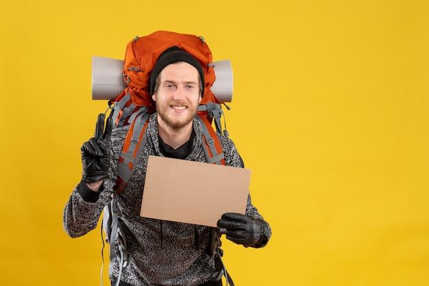 Auto-stoppeur masculin souriant avec des gants en cuir et un sac à dos tenant un carton vierge faisant le signe de la victoire