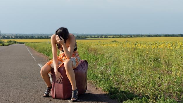 Auto-stoppeuse découragée en talons aiguilles et une robe d'été assise sur une grande valise le long d'une route de campagne avec sa tête dans ses mains
