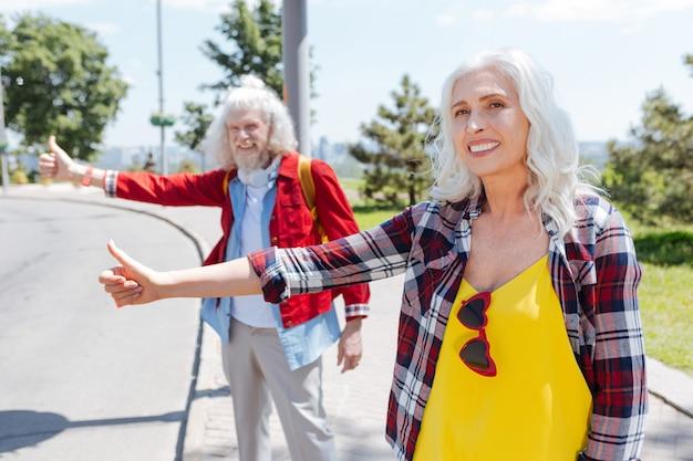 Auto-stoppeuse féminine. ravi de femme âgée souriant tout en cherchant une voiture pour un tour