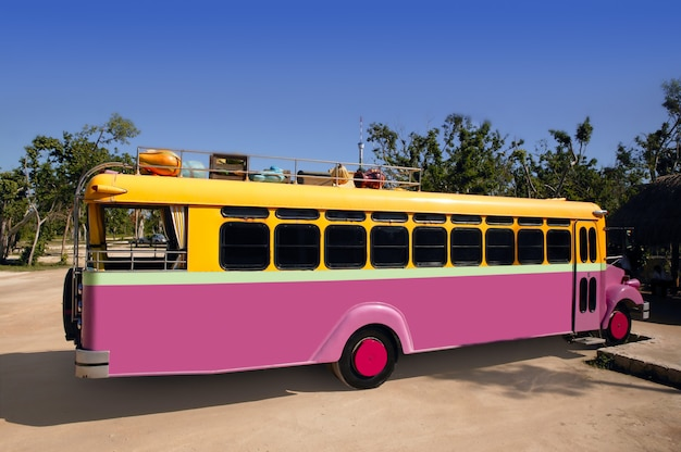 Autobus coloré jaune et rose touristique tropical