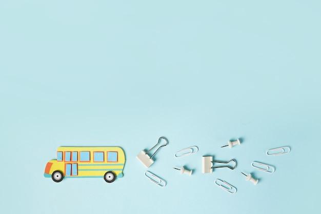 Autobus scolaire de coupe de papier sur la scène bleue. fait main. espace de copie