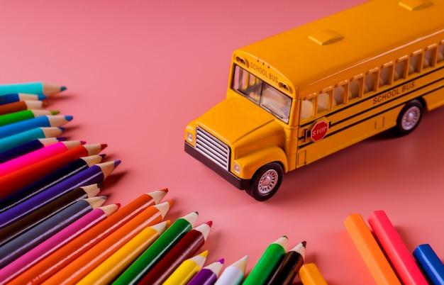 Autobus scolaire jouet avec des crayons de couleur sur fond rose.