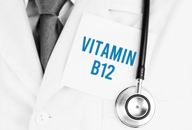 Autocollant blanc avec texte vitamine b12 allongé sur une robe médicale avec un stéthoscope