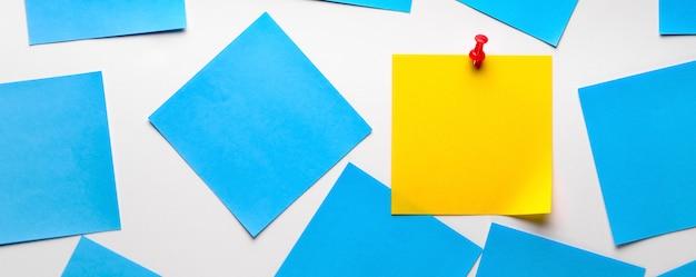 Autocollant collant jaune pour rappel d'information. espace pour le texte. à côté se trouvent des autocollants bleus vides. bannière