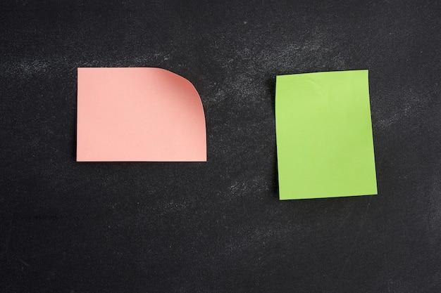 Autocollant papier rose et vert vierge collé sur un tableau noir