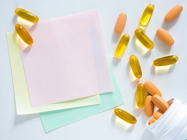 Un autocollant et une poignée de pilules sont sur un tableau blanc, copiez l'espace, vue de dessus, plat, gros plan