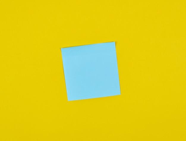 Autocollants carrés de papier bleu vide sur jaune