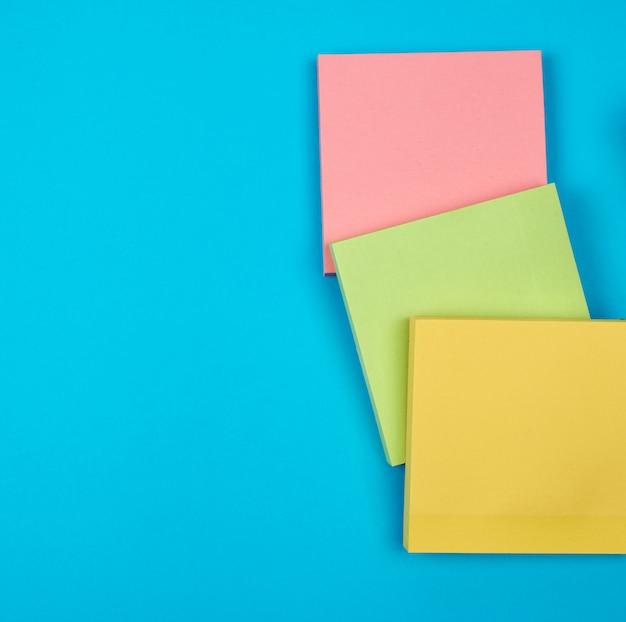 Autocollants carrés papier multicolore vide sur fond bleu