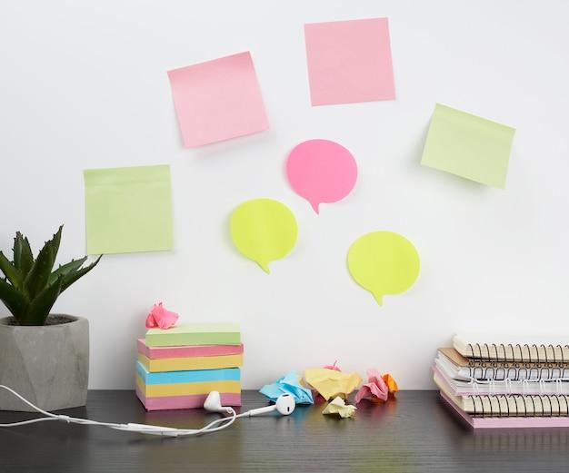 Des autocollants colorés fixés à un mur blanc, une pile de bloc-notes posée sur la table