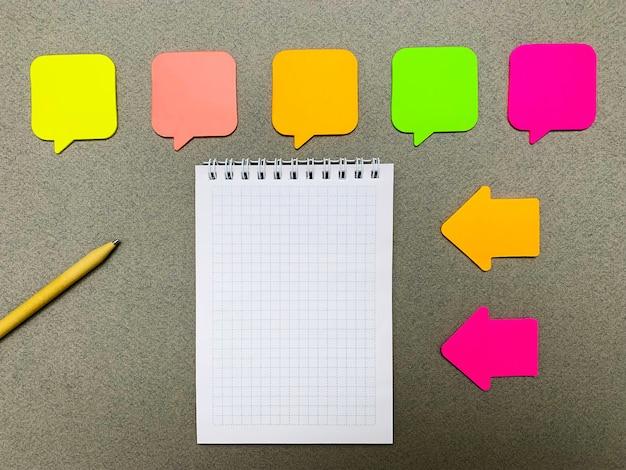 Autocollants avec un espace vide pour le texte sur un mur gris avec carnet et crayon