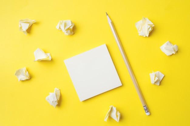 Autocollants jaunes, papier froissé et un crayon