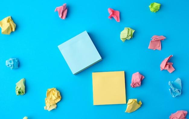 Autocollants en papier blanc multicolore de différentes couleurs sur fond bleu