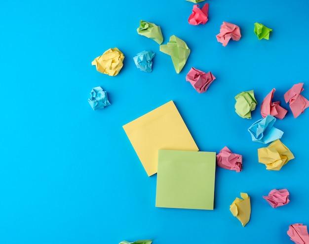 Autocollants en papier blanc multicolore de différentes couleurs sur une surface bleue