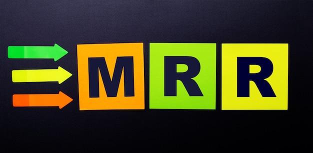 Autocollants en papier multicolore lumineux sur fond noir avec le texte mrr