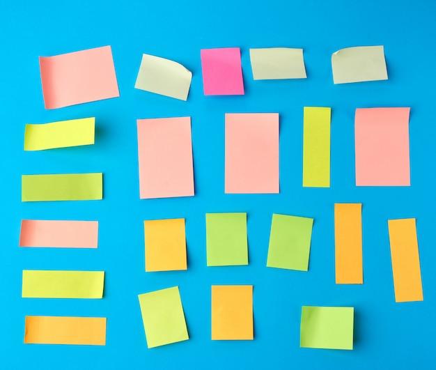Autocollants en papier multicolores de différentes formes sur fond bleu