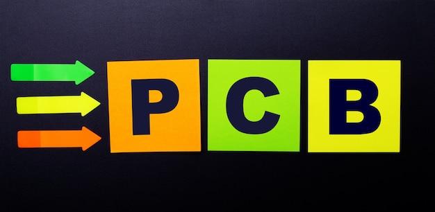 Autocollants en papier multicolores lumineux sur fond noir avec le texte pcb printed circuit board