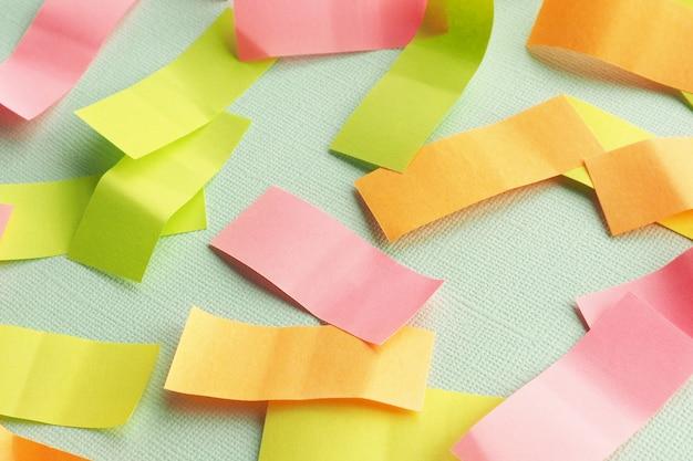 Autocollants rectangulaires multicolores sur un papier bleu texturé.