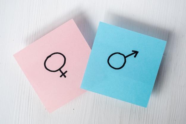 Des autocollants avec des symboles de genre vénus et mars indiquent un homme et une femme sur fond blanc