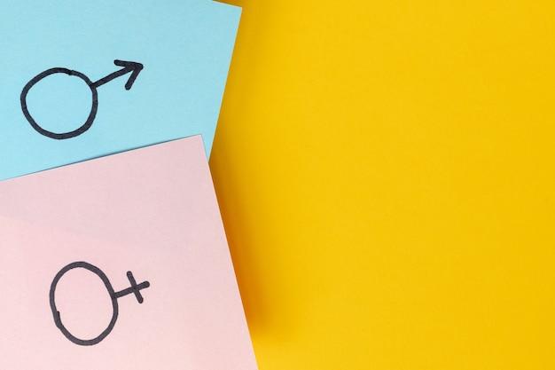 Des autocollants avec des symboles de sexe vénus et mars indiquent un homme et une femme sur un fond jaune