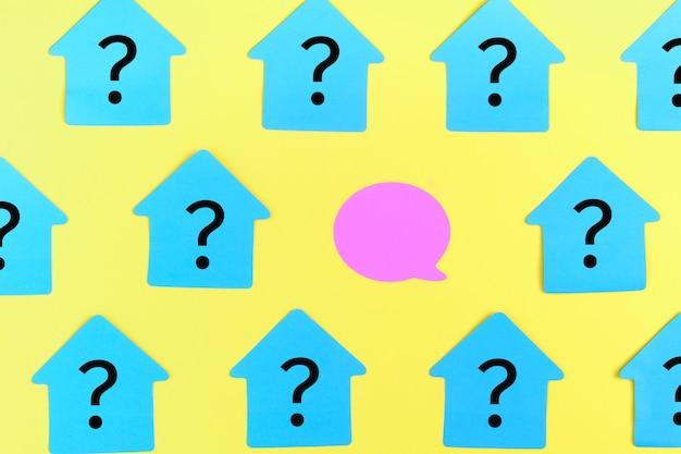Autocollants turquoises en forme de maison, avec des points d'interrogation.