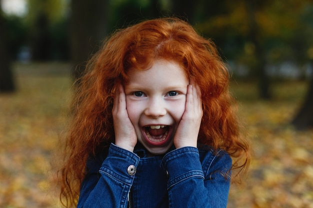Automne automne, portrait d'enfant. charmante et rousse petite fille a l'air heureux marchant et jouant sur t