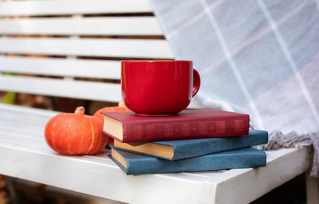 En automne, sur un banc, une tasse de thé, des livres, des carreaux à carreaux, de la citrouille dans le jardin. humeur d'automne et lecture.