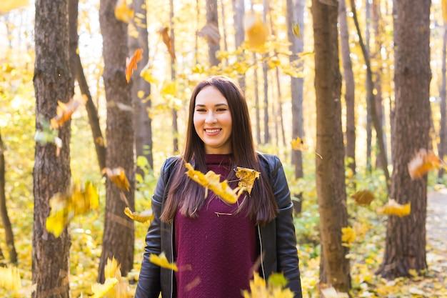 Automne, beauté, concept de personnes - jeune femme posant dans un parc d'automne avec des feuilles qui tombent.