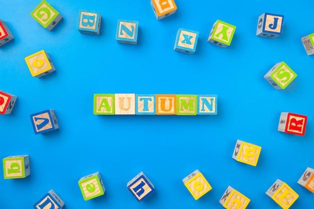 L'automne. blocs d'alphabet en bois coloré sur papier bleu