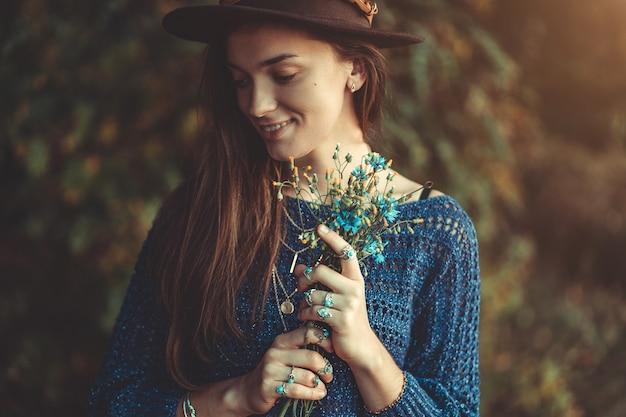 Automne brunette boho chic femme dans un chapeau brun et pull bleu tricoté avec bouquet de fleurs sauvages dans les mains dans la forêt d'automne à l'extérieur à l'automne