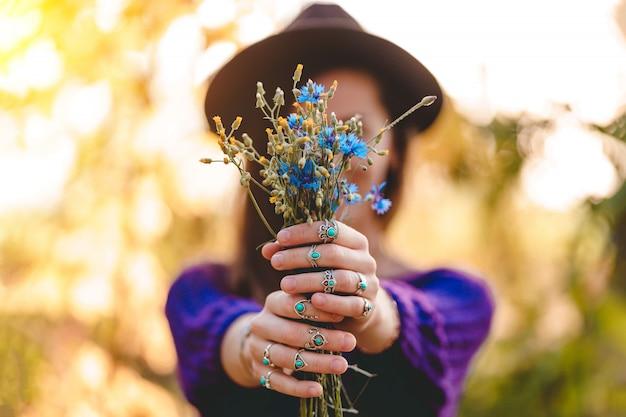 Automne brunette woman wearing silver rings avec turquoise stone détient bouquet de fleurs sauvages dans les mains dans la forêt d'automne à l'extérieur à l'automne