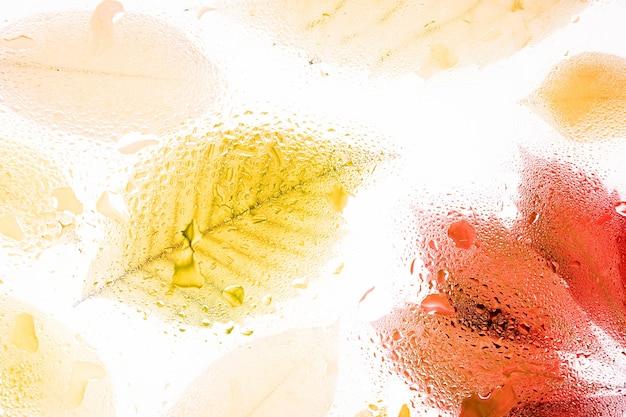 L'automne jaune laisse derrière un verre brumeux avec des gouttes d'eau et de la pluie tombe abstrait
