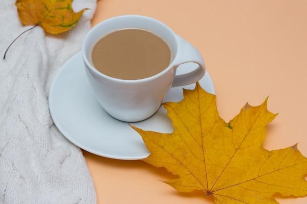 L'automne laisse une tasse de café chaud avec un pull chaud blanc laiteux